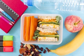 School lunch box with sandwich, vegetables, water, nuts and fruits on turquoise background. Healthy eating habits concept