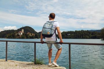 Tourist man sitting on the lake and enjoying the view.