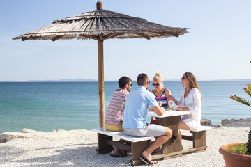 Group of friends sitting at table in beach bar
