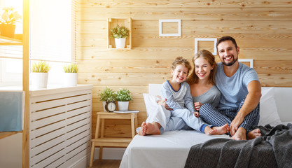 happy family mother, father and child   laughs in bed