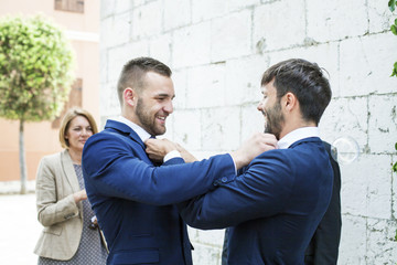 Groom and friend adjusting bow ties of each other