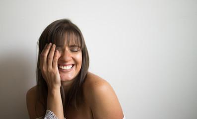 Mujer joven y sonriente con su mano en el rostro