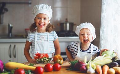 Healthy eating. Happy children prepares  vegetable salad in kitchen