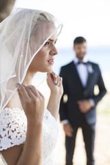 Bride adjusting veil, groom in background