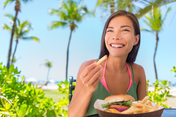 Woman eating french fries food at resort restaurant. Asian girl enjoying summer vacation at beach bar with fast food lunch meal, burger and fries.