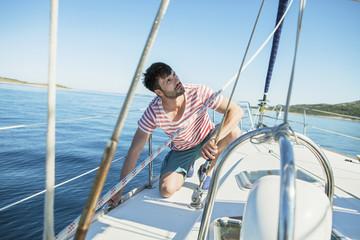Man adjusting rigging on sailboat, Adriatic Sea
