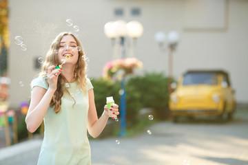 happy woman blowing soap bubbles. focus on soap bubbles