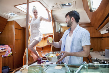 Young couple cooking in galley of yacht,, Adriatic Sea