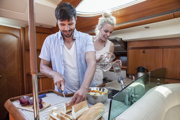 Young couple cooking in galley of yacht, Adriatic Sea