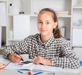 Teenage girl preparing for exams. Teenage girl doing homework for school..