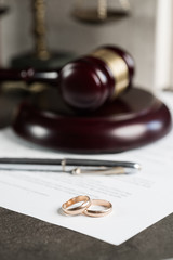 Image of wedding rings on wooden gavel at table in courtroom