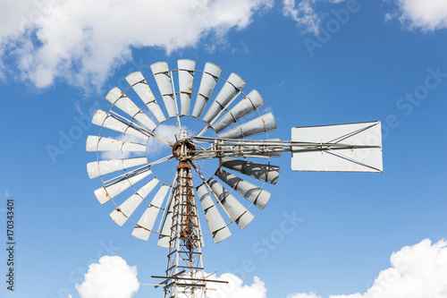 wind powered water pump against partly cloudy sky stock photo and