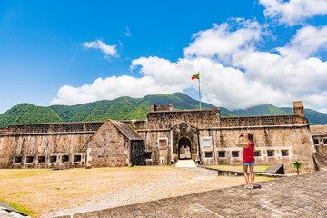Cruise tourist at St Kitts Brimstone Hill Fortress on vacation on St Kitts and Nevis. Caribbean cruise ship destination. Girl standing taking photo using smart phone camera on holidays.
