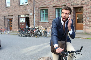 Shocked businessman riding a bicycle while talking on the phone