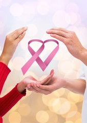 Open hands together with pink ribbon for breast cancer awareness