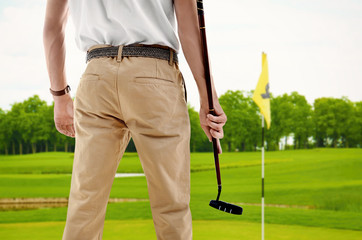 Young man playing golf on course