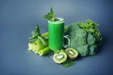 Glass of green healthy juice with ingredients on color background