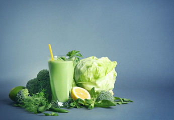 Glass of green healthy juice with vegetables and fruits on color background