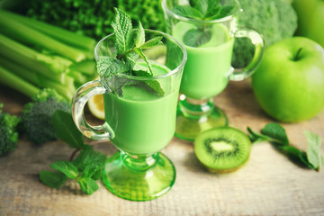 Glasses of green healthy juice with vegetables and fruits on wooden table