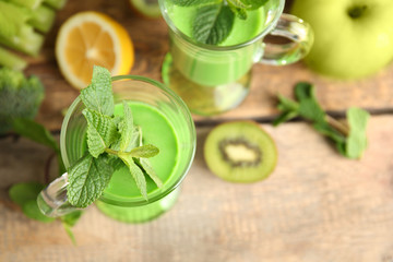 Glass of green healthy juice with fruits on wooden table