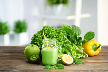 Mason jar of green healthy juice with vegetables and fruits on wooden table