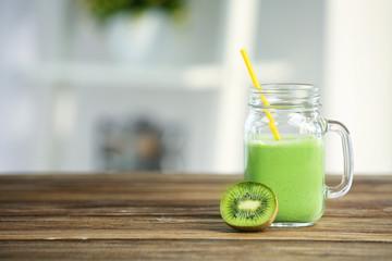 Mason jar of green healthy juice on wooden table
