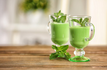 Glasses of green healthy juice with mint on wooden table