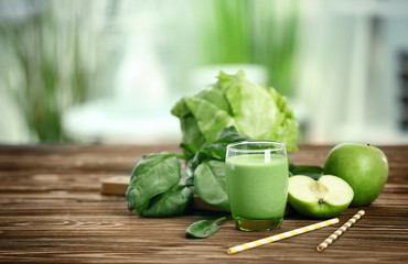 Glass of green healthy juice with ingredients on wooden table