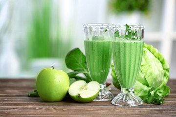Glasses of green healthy juice with ingredients on wooden table