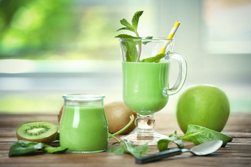Glass and jar of green healthy juice with fruits on wooden table