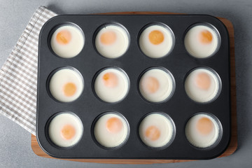 Muffin tin with baked eggs on table
