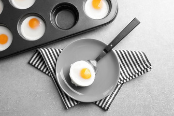 Plate with baked egg and muffin tin on table