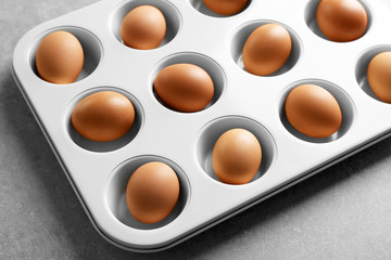Muffin tin with hard boiled eggs on table