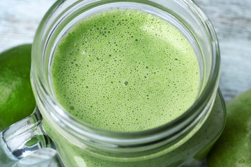 Mason jar of green healthy juice with fruits, closeup