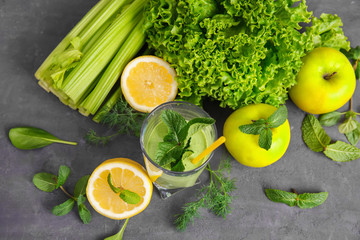 Glass of green healthy juice with fruits and vegetables on table