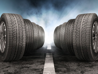 Car tires standing on the road against light of headlights.