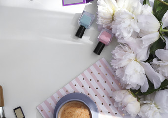 Bouquet of beautiful peony flowers, cup of coffee and cosmetics on light table