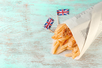 Fried fish and chips in a paper cone on wooden background