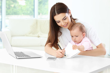 Young mother holding baby while writing in notebook in home office