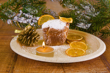 Christmas pudding with sugar orange, a burning candle and a golden bump on the background of a Christmas tree.