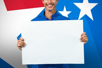 Composite image of portrait of happy man holding placard