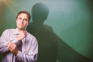 Composite image of portrait of young businessman adjusting shirt