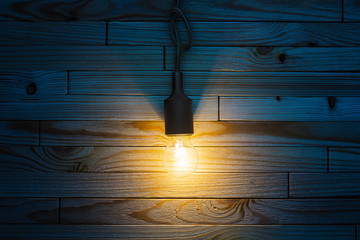 Burning incandescent bulb on a wooden background. A layout with an empty space for your text top view