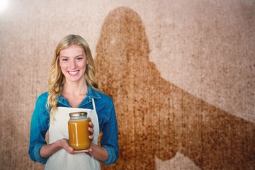 Composite image of portrait of young woman holding jar
