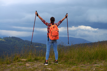 Young female with hiking poles outstretched hands
