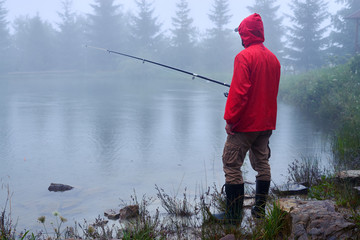 Papiers peints Peche Man in waterproof jacket fishing on lake