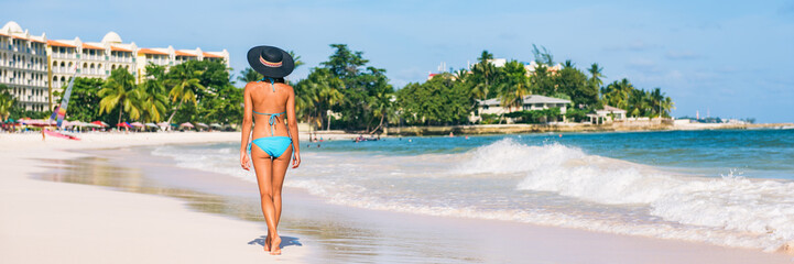 Wall Mural - Antigua beach woman on cruise vacation travel in Caribbean island. Bikini girl walking on white sand wearing sun hat relaxing on idyllic paradise tourist attraction.