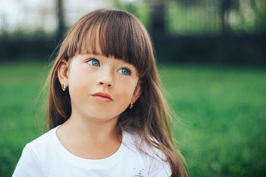 close up portrait of little dreaming girl with blue eyes