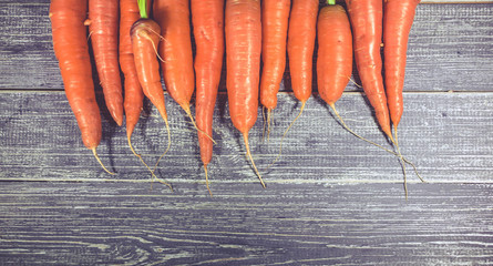 Fresh carrots on a wooden table. Healthy food background. Top view