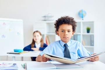 Cute boy with open book sitting by desk at reading lesson